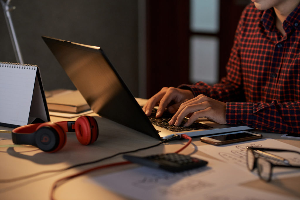 Hands of software engineer working on project at his table late at night